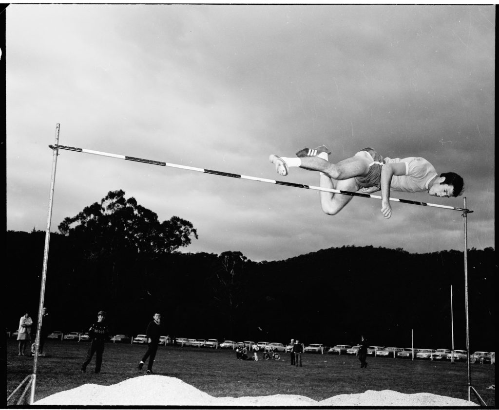 Black and white photograph of Laurie Peckham clearing the top of the high jump bar.