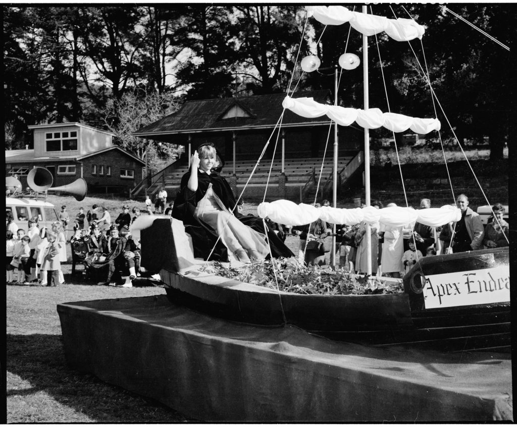 Black and white photograph of a woman in float of a sailing boat named 'Apex Endeavour' with crowd visible behind.