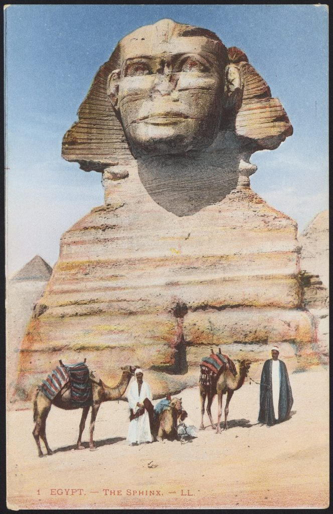 Colour image of the Sphinx with men and camels standing in front.