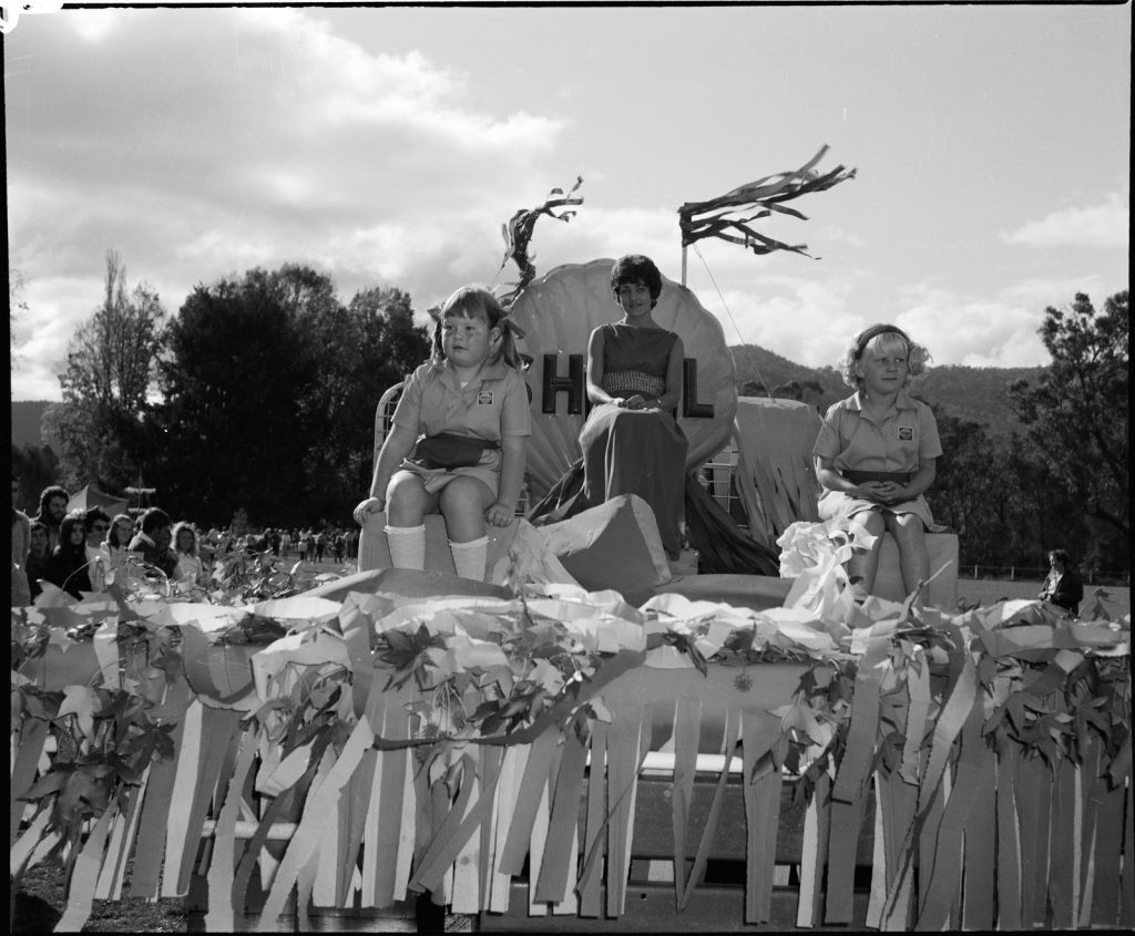 Black and white photograph of a parade float featuring a woman sitting on a 'shell' chair behind two young girls at the front of the float