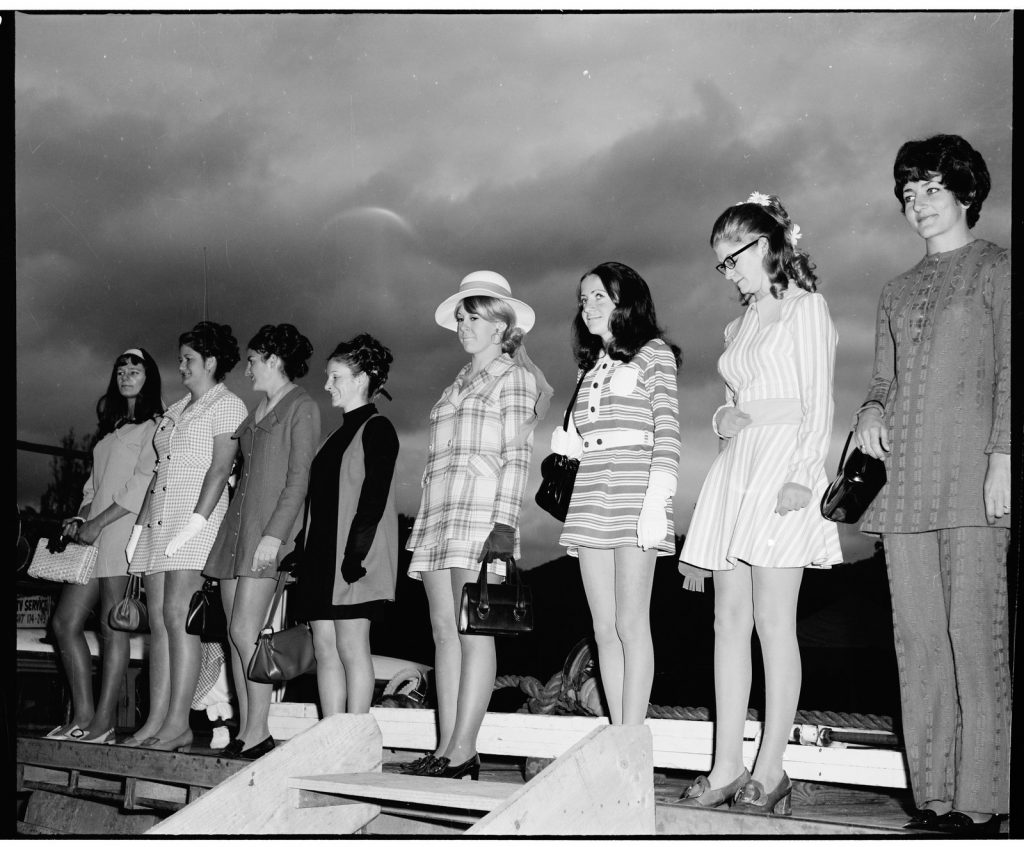 Black and white photograph of a line of women standing on a stage