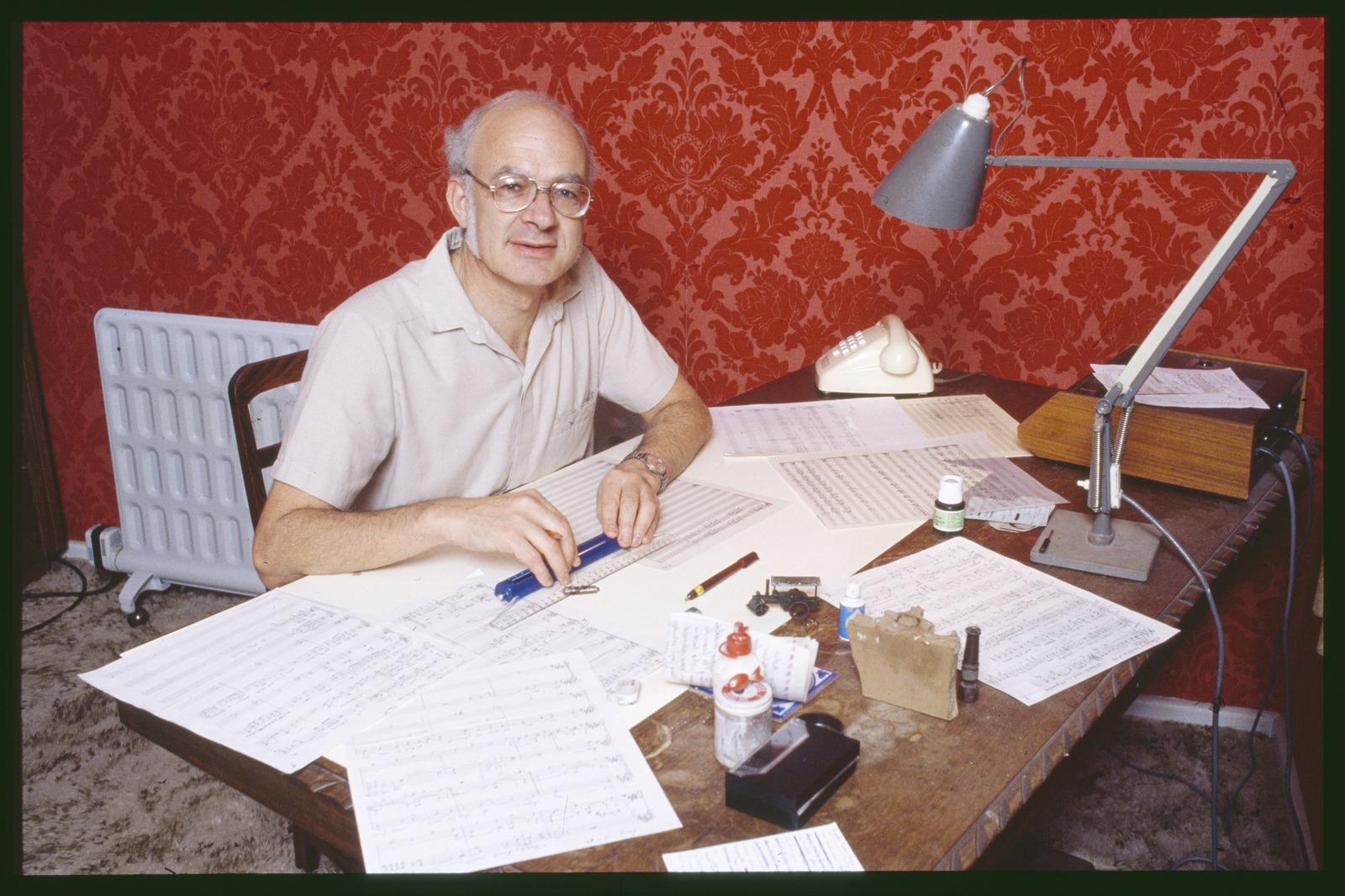 George Dreyfus sitting at his desk