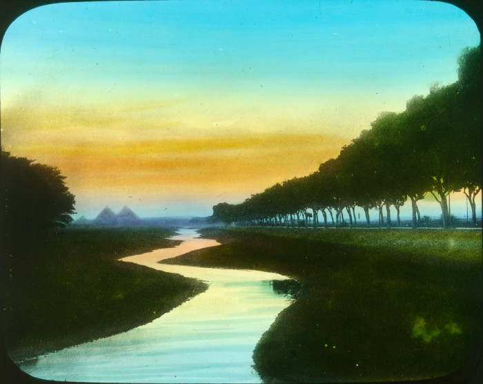 Picture shows winding river at sunset flanked by avenue of trees on eithr side
