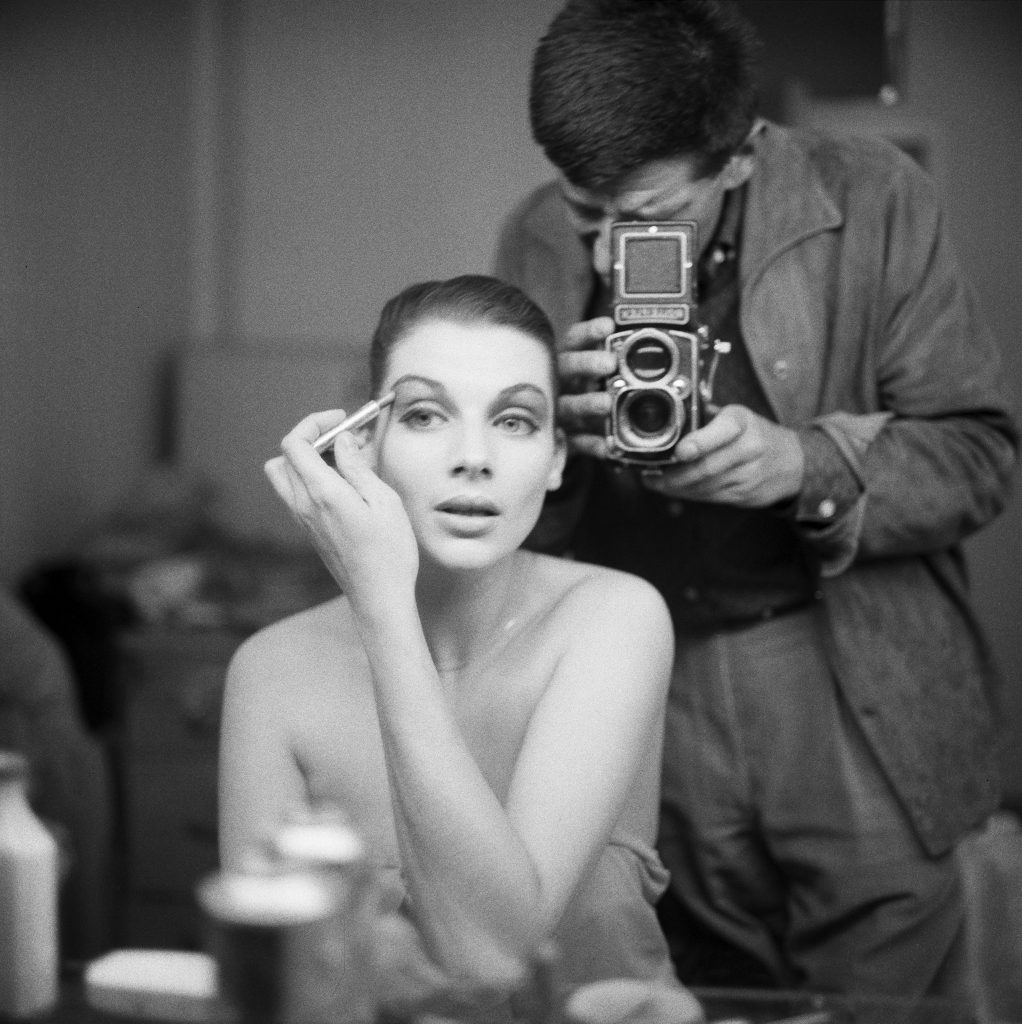 Photograph of model Maggie Tabberer seated in front of a mirror putting on makeup, photographer visible in mirror reflection, standing behind her, taking her picture, likely Henry Talbot.
