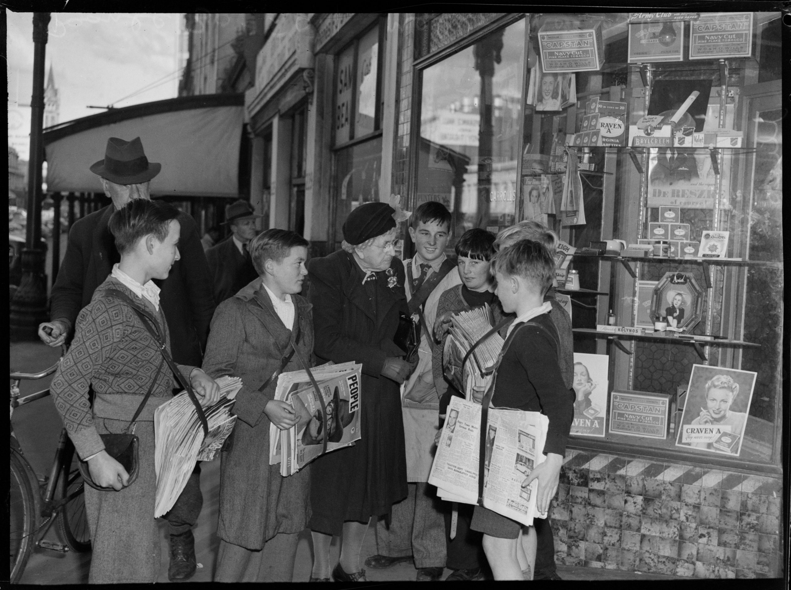 Black and white photo of Edith Onians standing with a group of newsboys in the street