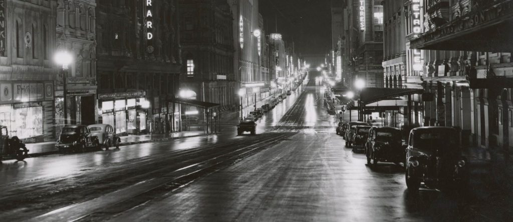 Black and white photograph of Melbourne's Bourke Street at night.