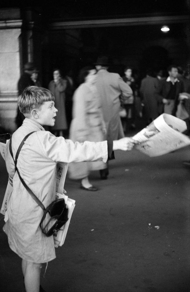 Black and white photo of a newspaper boy selling papers outside a Melbourne railway station