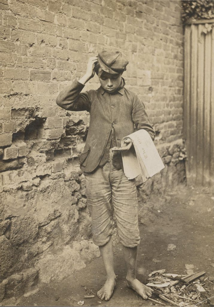 Black and white photo of 19th century newsboy in barefeet with knee length pants, jacket and cap