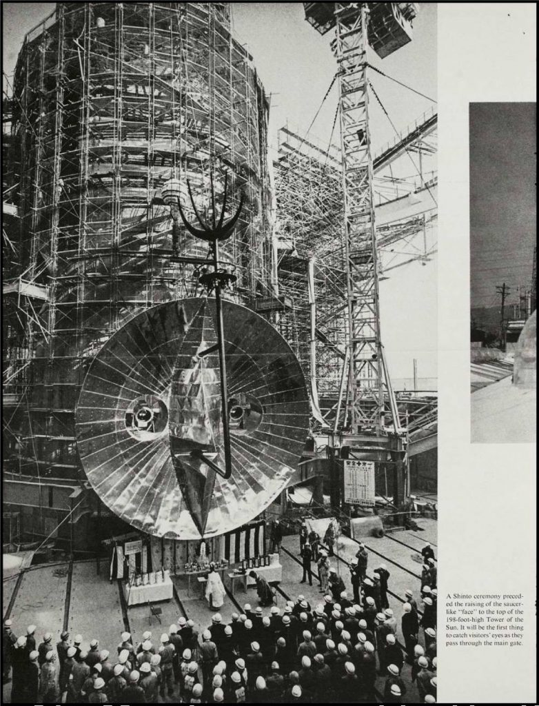 """Photo: a Shinto ceremony preceded the raising of the saucer-llike """"face"""" to the top of the 195-foot-high Tower of the Sun."""